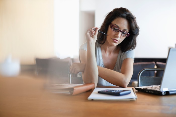 A bespectacled woman holding a pen close to her face as she's staring at a calculator on top of a notebook.