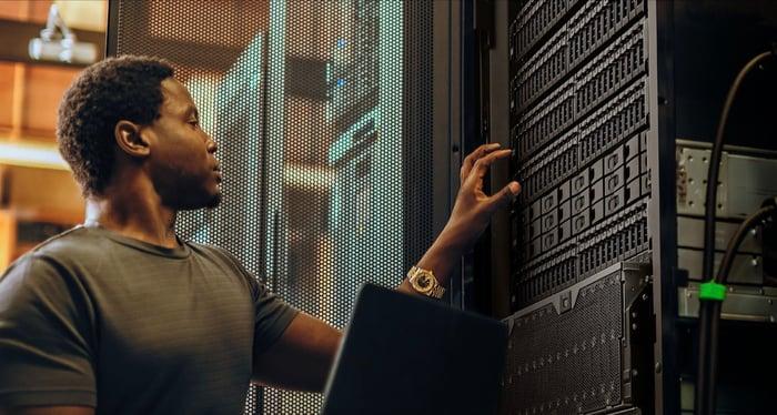 A man working on hard drives inside a data center.