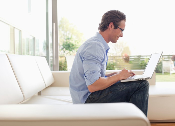 Man sitting on couch typing on laptop