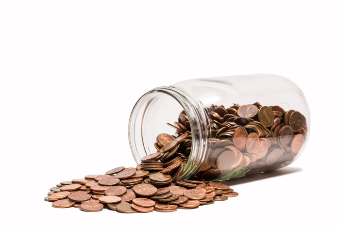 A jar without a lid has tipped over, spilling pennies everywhere.