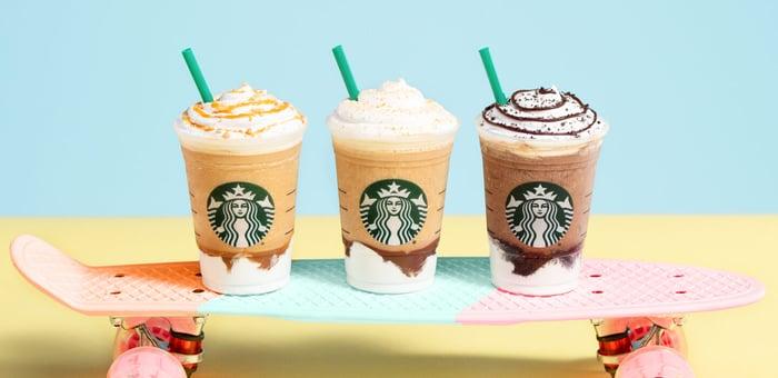Three Starbucks Frappuccinos sitting on a skateboard