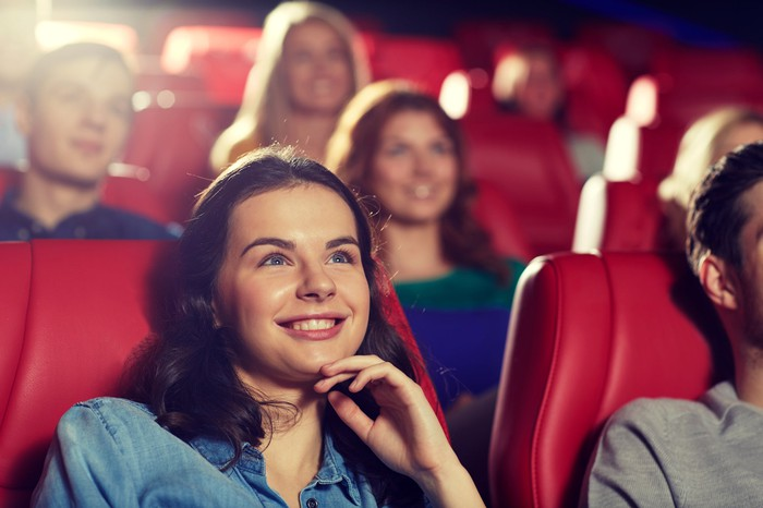 Woman smiling in a movie theater while she watches a film