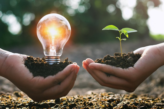 two hands holding dirt with light bulb and green plant sprout indicating clean energy
