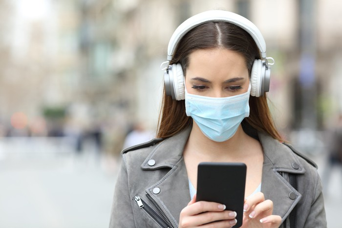 A young woman uses her smartphone, wearing a surgical mask and white headphones.