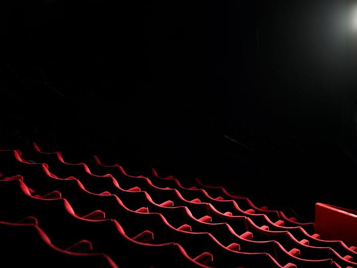 Empty seats in a dark movie theater.