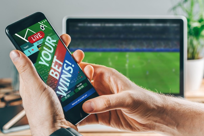 "A phone with the words ""your bet wins"" on it and a soccer match playing on a screen behind the phone."