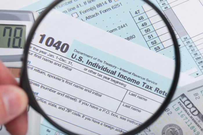 A person holding a magnifying glass above an IRS 1040 tax form.