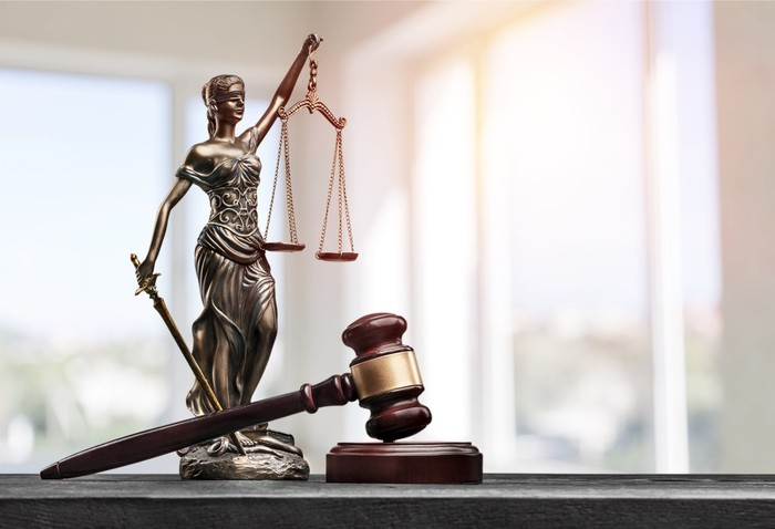 blind justice statue holding the scales next to a court gavel