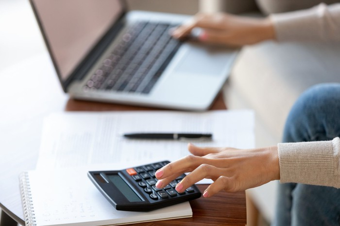 A taxpayer calculates her taxes on a calculator and laptop.