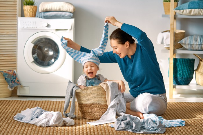 A mother and child play with laundry, with a laundry machine and some shelves in the background.