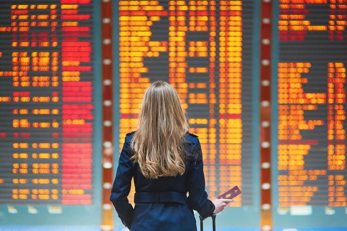 A woman looks at the board in an airport for flight information.