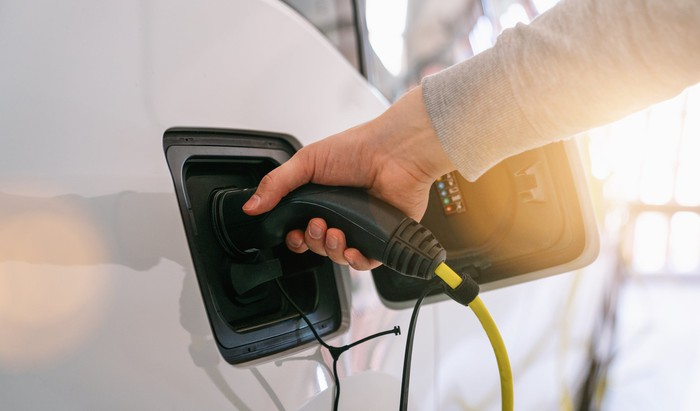 Man's hand plugging a charger into an electric car port