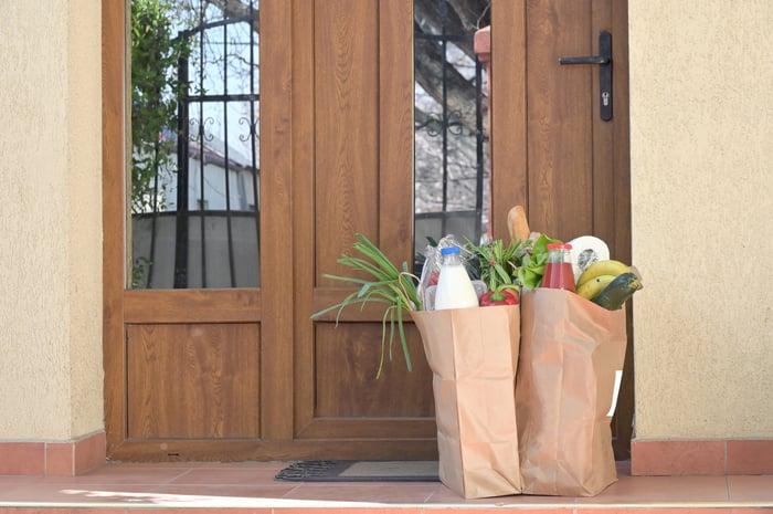Groceries in bags on a doorstep.