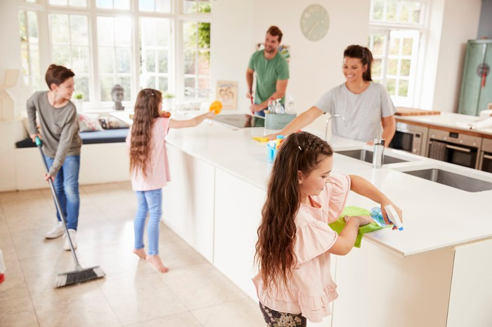 family cleaning floor and counters together in kitchen