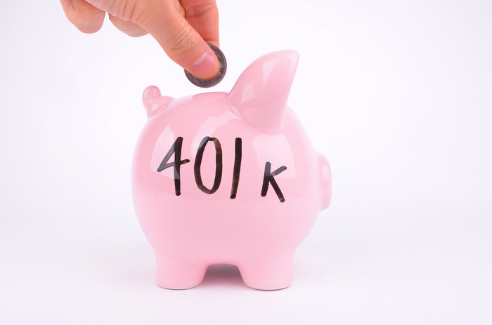 A hand is dropping a coin into a pink piggy bank on which is written 401k.