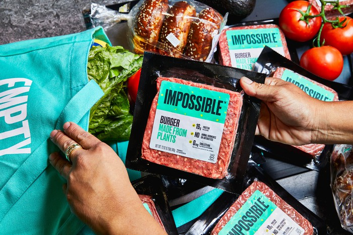 A shopper with various products holds a package of Impossible Burger.