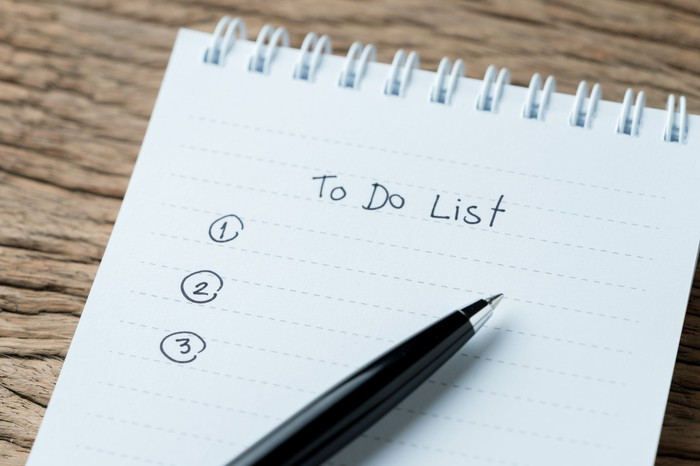 Pen resting on a paper pad with a blank to-do list written on it.
