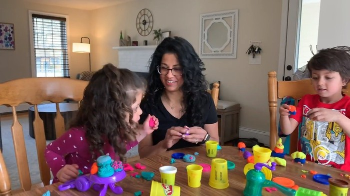 An adult and two children playing with Hasbro's Play-Doh.