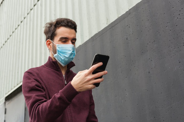 A masked man looks at his smartphone while walking beside a building.