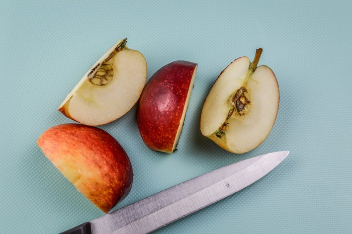 A knife placed below an apple cut into quarters.