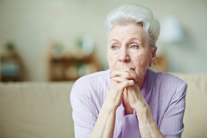 Pensive-looking older woman sitting on a sofa with her hands clasped in front of her mouth.