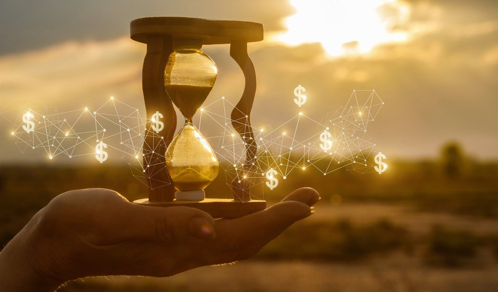 hourglass and money in hand