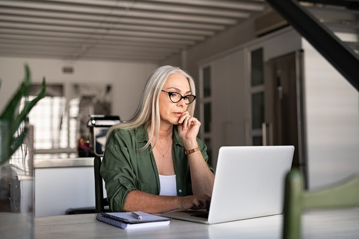 Woman with glasses sitting at her kitchen table and staring at her computer screen.