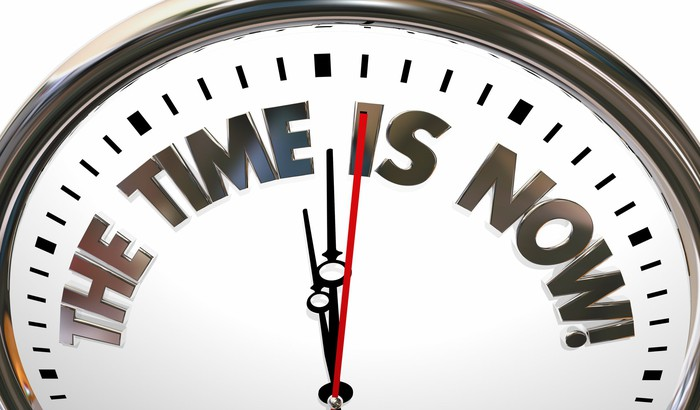 """A clock displays the phrase """"the time is now"""" instead of numbers."""