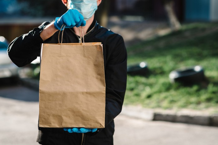A man holds a brown bag with food while wearing a face mask and gloves.