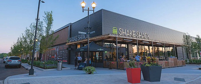 A Shake Shack storefront is seen under a blue sky.