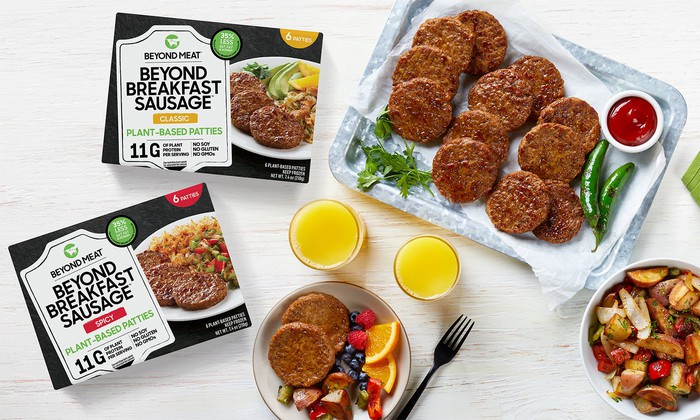Beyond Breakfast Sausage from Beyond Meat displayed in and out of packaging next to breakfast food items on a table.