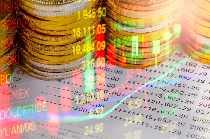 Stacks of gold coins on financial charts.
