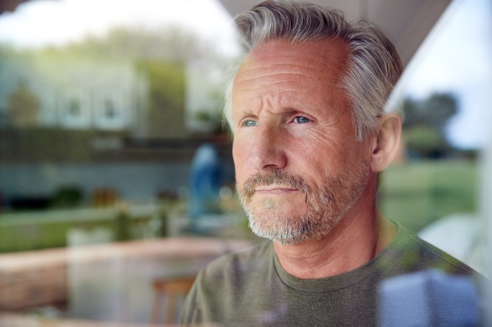 Close-up of older man looking out window.