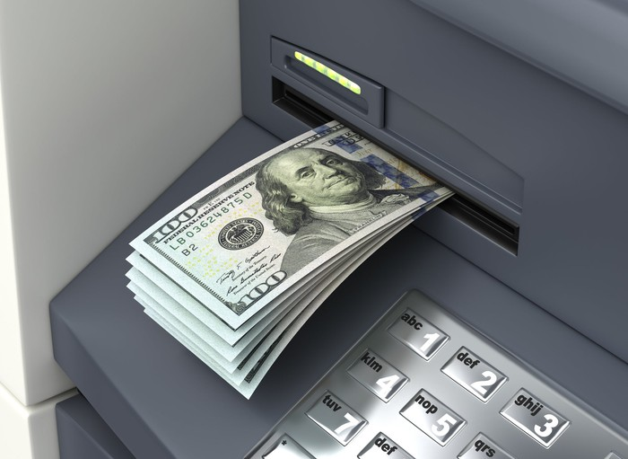 A stack of $100 bills being dispensed from an ATM.
