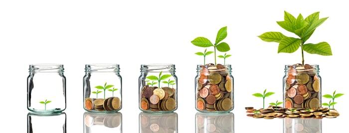 Plants growing in  increasingly full jars of coins.