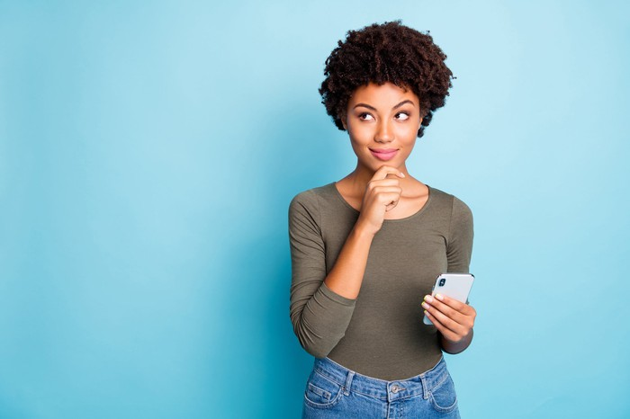 Woman looking away and thinking as she holds her smartphone.