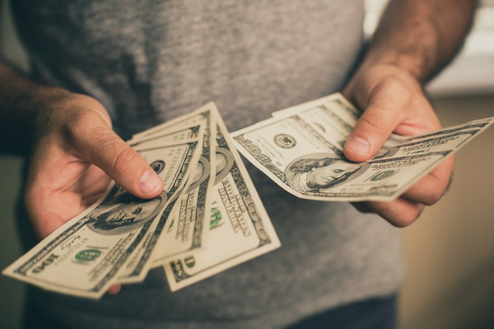 A man's hands hold a group of $100 bills.