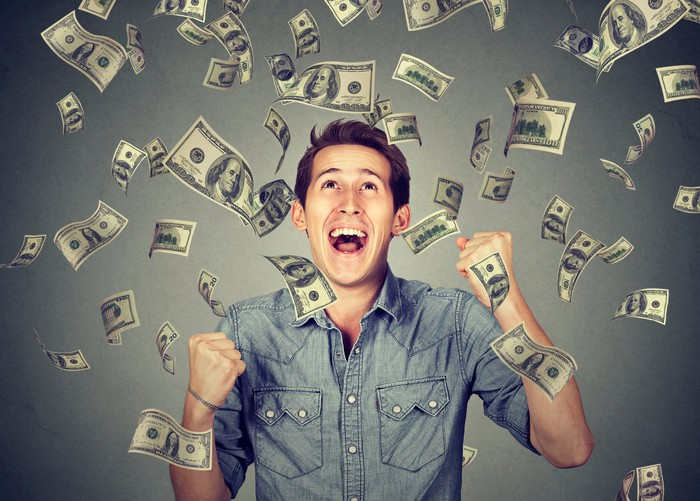 A smiling young man with fists raised as dollar bills rain down around him