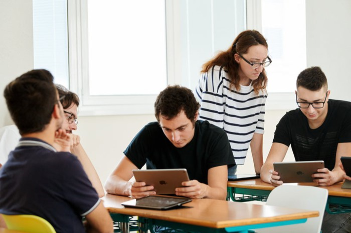 College students using iPads in a classroom.