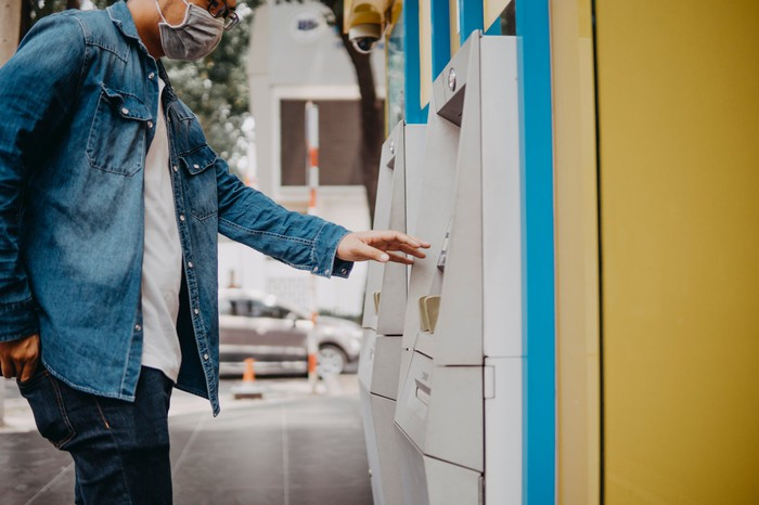 A consumer wears a mask and works an ATM machine.