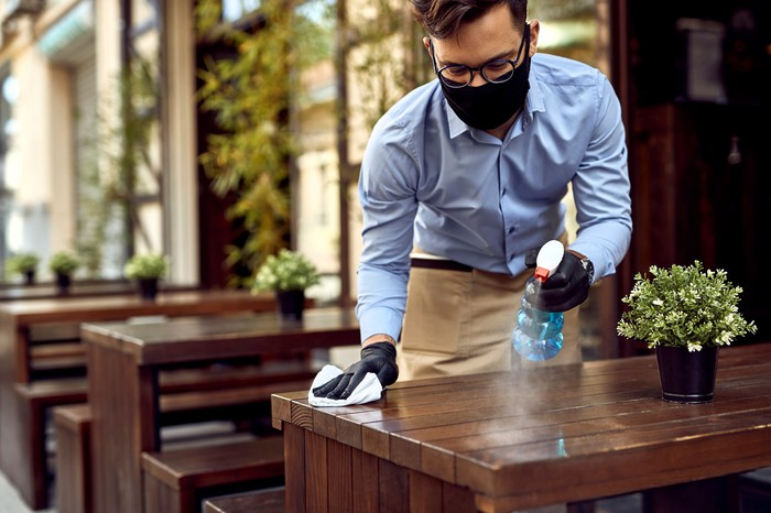 A waiter wears a mask and sprays disinfectant on the table.