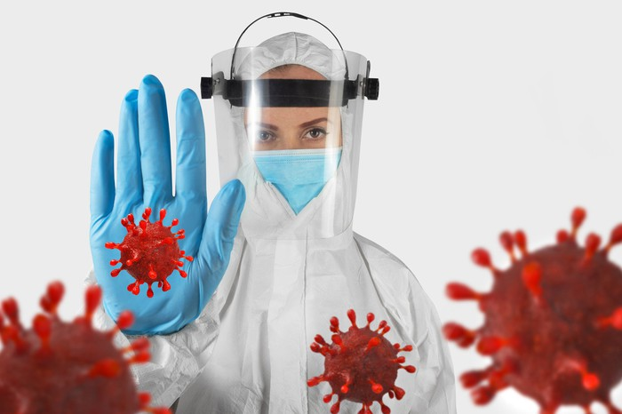 Scientist wearing protective gear, holding up a hand against several coronaviruses