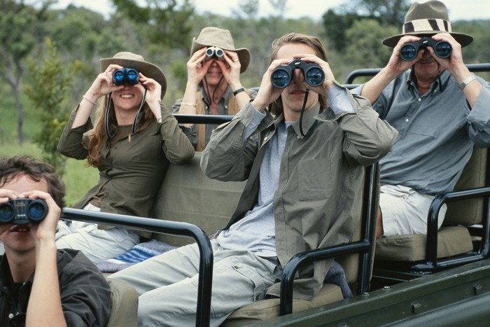 A traveling family sits on a Jeep and looks at camera with binoculars.