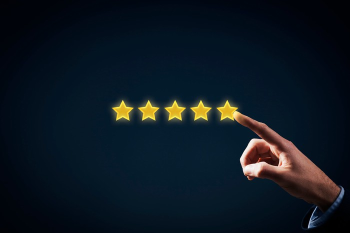 A hand pointing to a five-star rating