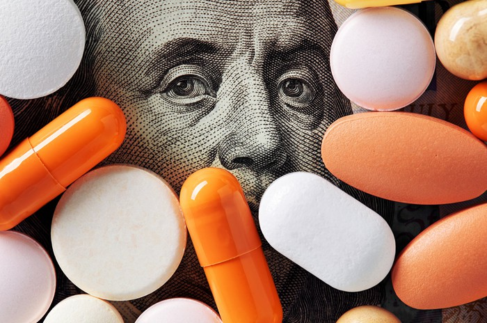 the picture of Ben Franklin on the hundred dollar bill looks out from among a colorful collection of pills and tablets.