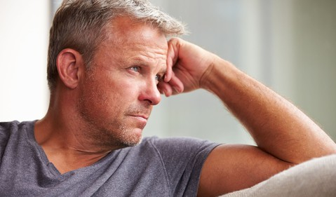 mature man looking out window worried concerned sad