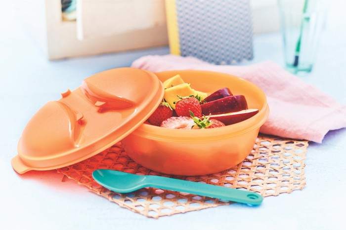 A plastic Tupperware container filled with fresh fruit