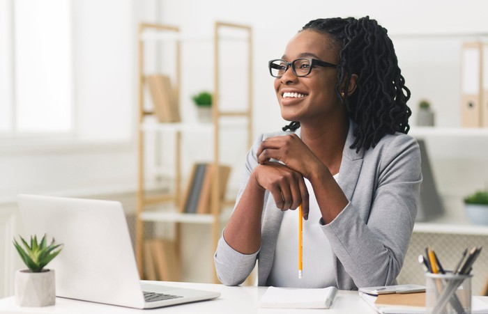A woman smiles at her desk in an office.