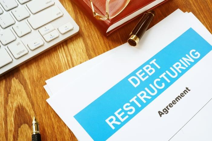 A written debt restructuring agreement lying on a wooden desk