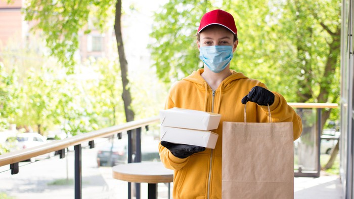 A food service employee delivers food while wearing a mask and gloves.